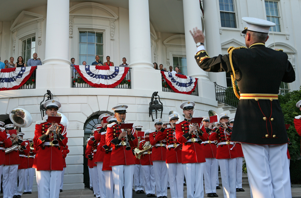 The band plays as President Barack Obama (L) and first lady Michelle Obama stand on the balcony as families gathered for Independence Day festivities on the South Lawn White House July 4, 2010 in Washington, DC.