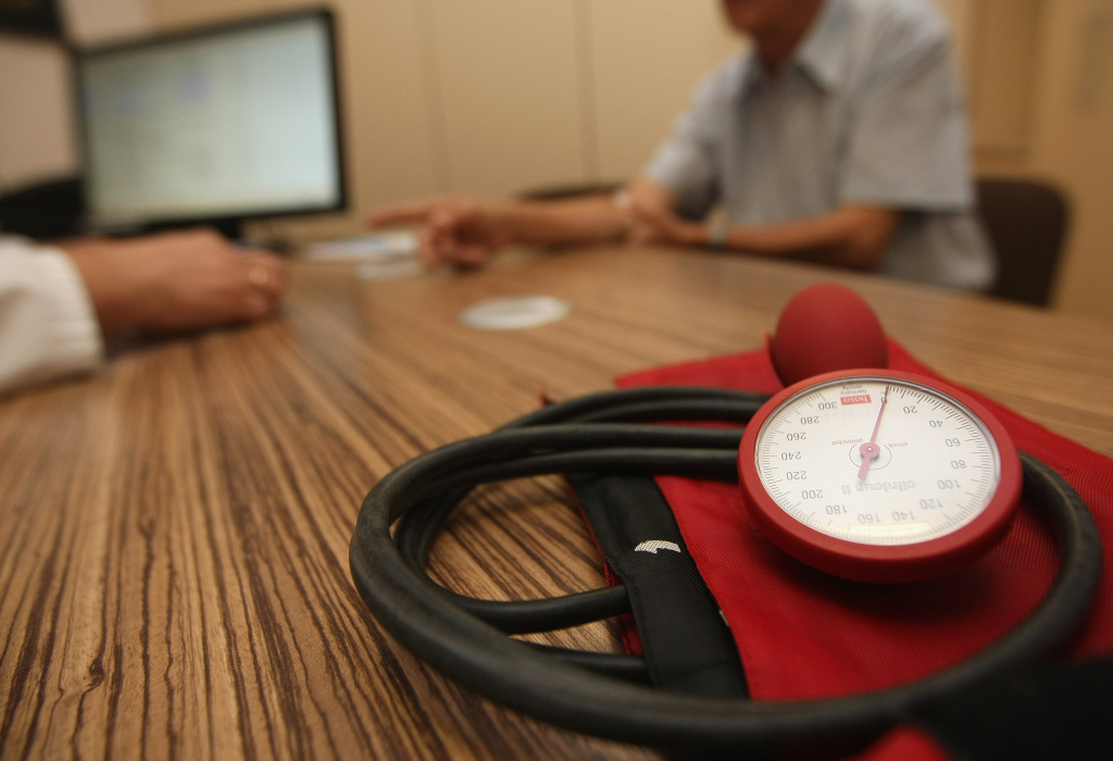 A doctor speaks to a patient as a sphygmomanometer, or blood pressure meter, lies on his desk on September 5, 2012 in Berlin, Germany.