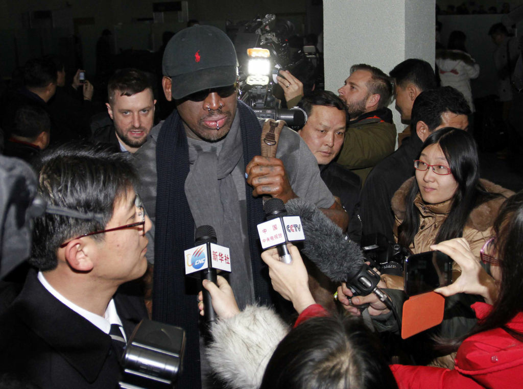 Flamboyant former NBA star Dennis Rodman is surrounded by journalists upon arrival at Pyongyang Airport, North Korea, Tuesday, Feb. 26, 2013. The American known as