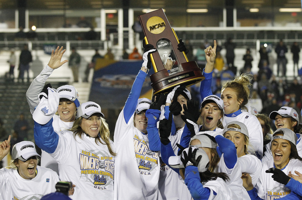 UCLA players and head coach Amanda Cromwell, second from left, celebrate with the trophy after beating Florida State 1-0 during overtime in the championship soccer game at the NCAA Women's College Cup in Cary, N.C., Sunday, Dec. 8, 2013.