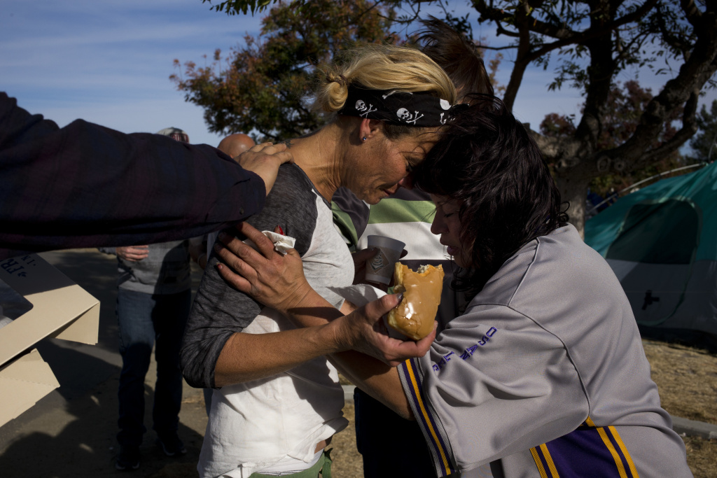 Amy Potter, left, and Victoria Pena, who are both homeless, pray for each other while holding donuts and coffee donated by local church members in a homeless encampment on the Santa Ana River trail Saturday, Dec. 9, 2017, in Anaheim, Calif. Goodhearted neighbors heartbroken over the rising number of homeless in their communities are dishing out hot meals, providing mobile showers and handing out sandwiches to those in need.