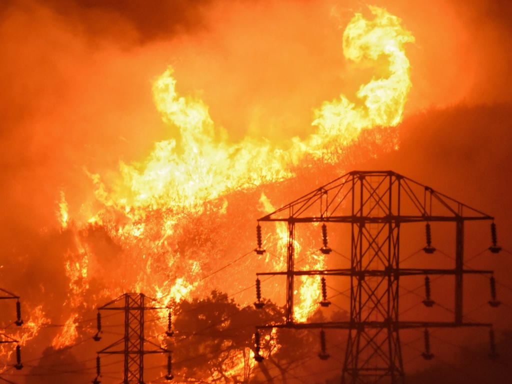 Flames burn near power lines in Montecito, Calif. State fire officials say power lines coming into contact with trees sparked four Northern California wildfires last October.