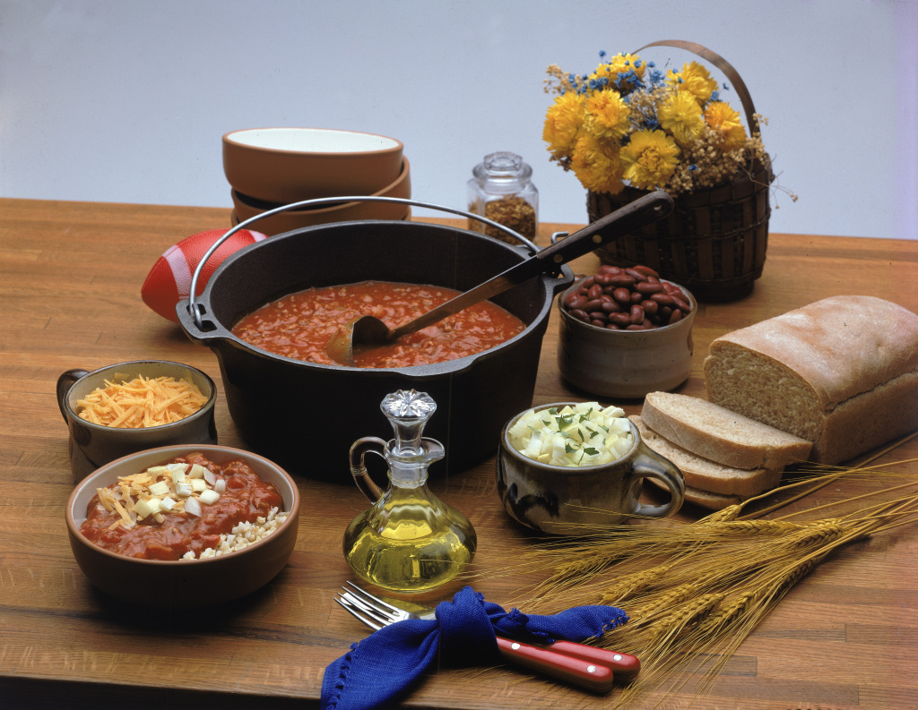 All the items necessary for a chili feast sit on a wooden surface.