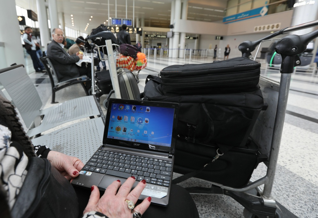 A Syrian woman travelling to the United States through Amman opens her laptop before checking in at Beirut international airport on March 22,2017.