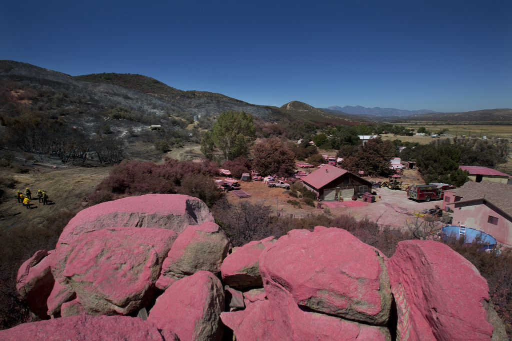 The San Bernardino National Forest team works on the Pilot Fire behind Ryan Nuckols's home in Hesperia California on August 9th, 2016. The pink fire retardant line is one of the reasons why fire crews were able to save Nuckols' house from the fire.