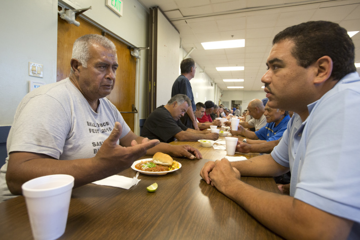 Rigoberto Bejarano (left) talks with intake coordinator Salvador Mendoza at Proyecto Pastoral. The group established The Guadalupe Homeless Project in 1988 to address what it saw as a neglected issue in the community: emergency shelter for the homeless.