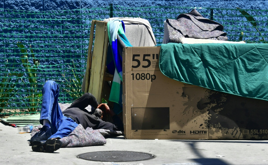 A homeless man sleeps beside his makeshift temporary shelter on a street in downtown Los Angeles, California.