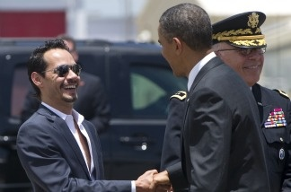 US President Barack Obama (R) greets singer Marc Anthony after disembarking from Air Force One upon arrival at Luis Munoz Marin International Airport in San Juan, Puerto Rico, June 14, 2011.