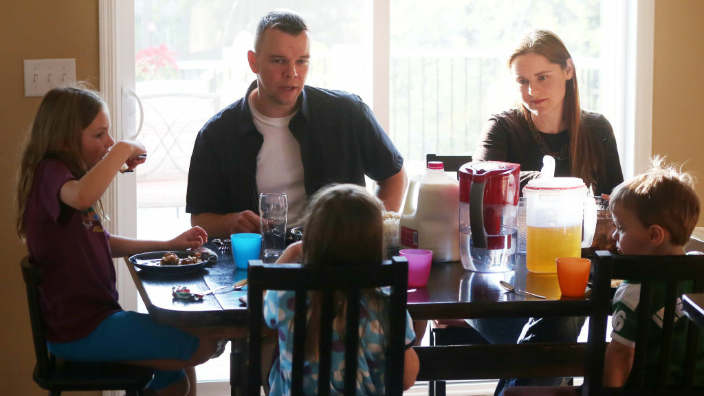 The Ross family eats dinner at their home in Mahtomedi, Minn. Kevin Ross joined the Minnesota National Guard in 1999.