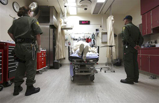 Correctional officers stand watch over an inmate receiving treatment in the emergency room at California State Prison, Corcoran, in Corcoran, Calif., Wednesday, Jan. 14, 2009. A federal court-appointed receiver says the state needs to pay $8 billion to upgrade prison's medical and mental health care.