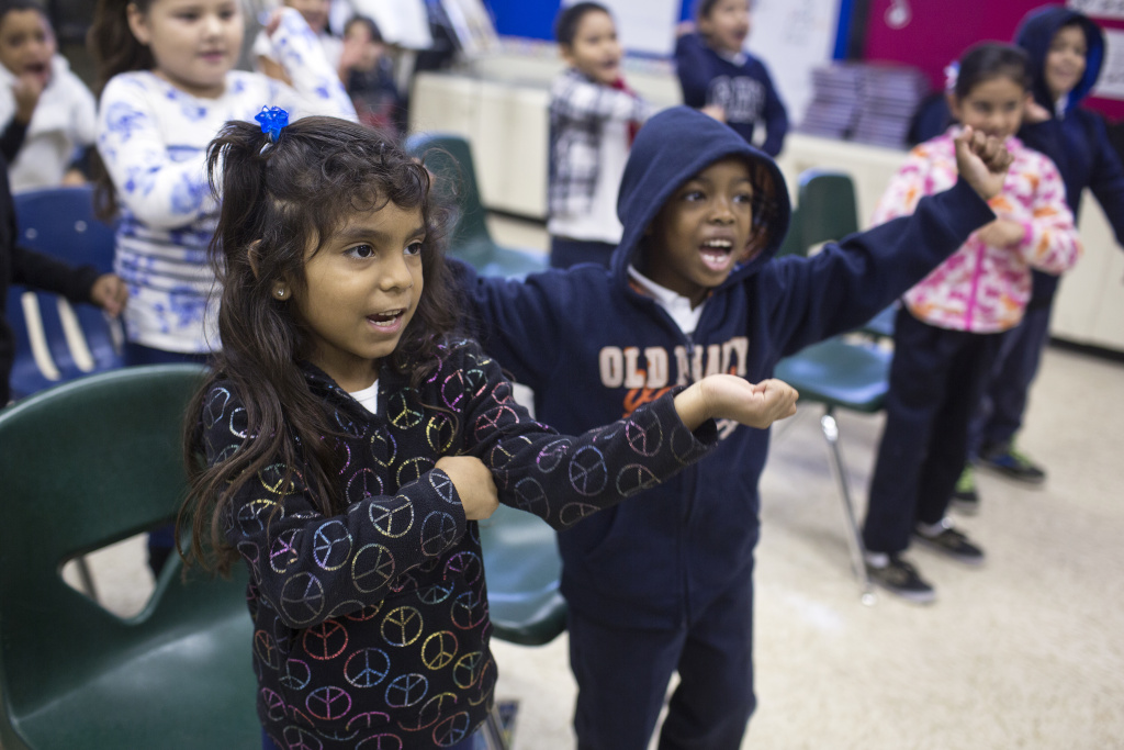 First graders Sherlyn Asuna, left, and Jaden Armstrong practice a holiday song at Martin Luther King Elementary School in Compton on Friday morning, Dec. 5, 2014.