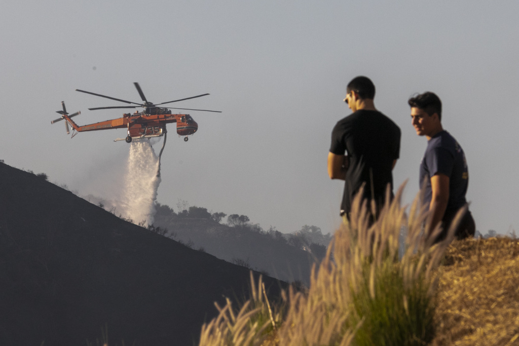 People watch helicopters make water drops on the Getty Fire on October 28, 2019 in Los Angeles, California.