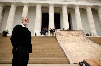 Laird Monahan stands on the steps of the Lincoln Memorial next to a giant banner printed with the Preamble to the United States Constitution during a demonstration against the Supreme Court's Citizens United ruling on the National Mall October 20, 2010 in Washington, DC.
