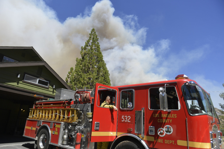 Firefighters work to save a home damaged by fire off Highway 138 Wednesday. The home caught on fire from embers thrown out by the Blue Cut Fire on Wednesday, Aug. 17, 2016.