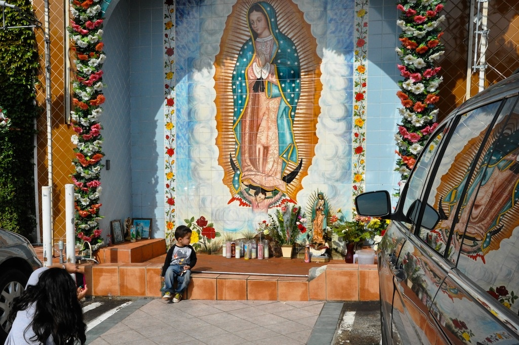 A woman takes a photo of a child in front of a shrine to the Virgin of Guadalupe outside of El Mercado in L.A.'s Boyle Heights.