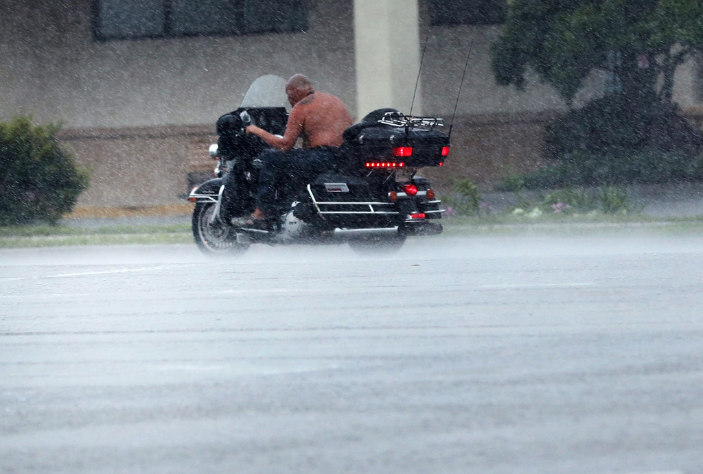 A man rides a motorcycle through the wind and rain as Hurricane Irma arrives on September 10, 2017 in Bonita Springs, Florida.