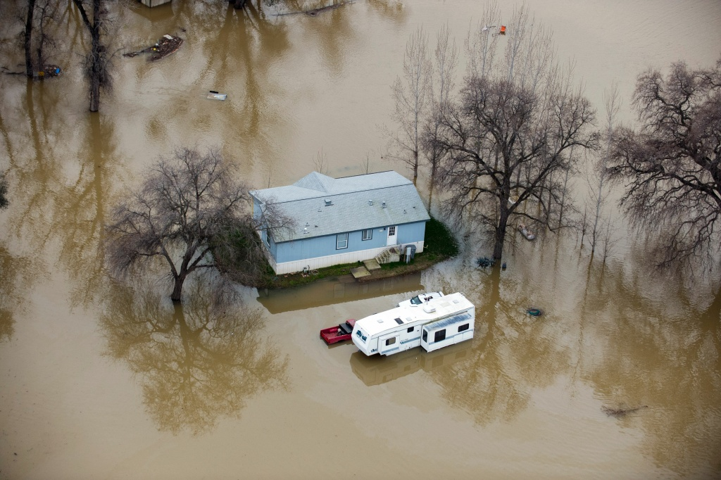 A home is seen marooned as the surrounding property is submerged in flood water in Oroville, California on February 13, 2017.