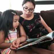 Cynthia Lopez reads to her 3-year-old, Ariani, in her Huntington Park home. She drives her daughter 12 miles to Silver Lake for preschool.