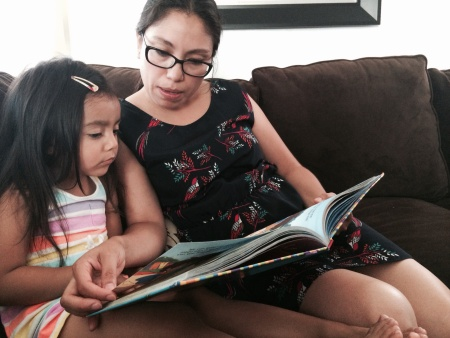 Cynthia Lopez reads to her 3-year-old, Arianni, in her Huntington Park home. She drives her daughter 12 miles to Silver Lake for preschool.
