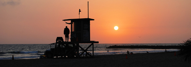 A lifeguard at a lifeguard tower at sunset in Newport Beach. The tradition of sitting around a bonfire at sunset may be banned from the beach.