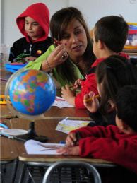 A teacher talks to a little boy on April 26, 2010 during her instruction at school