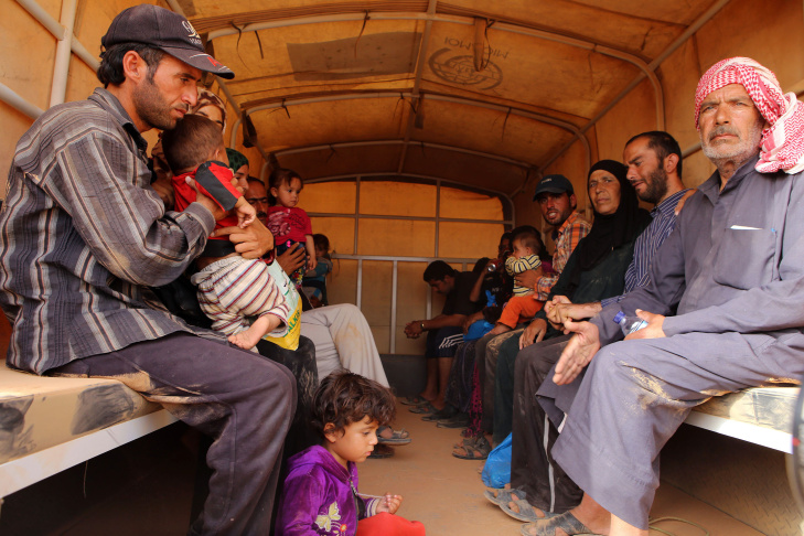FILE: Syrian refugees sit in a Jordanian army vehicle after crossing into Jordanian territory with their families on Sept. 10, 2015. The Trump administration's temporary travel ban suspends refugee entries to the United States unless refugees can prove they have a close family tie in the U.S.