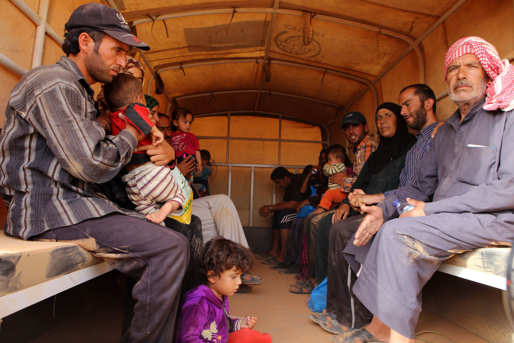 In this Thursday, Sept. 10, 2015 photo, Syrian refugees sit in a Jordanian army vehicle after crossing into Jordanian territory with their families near the northeastern Jordanian border with Syria and Iraq. The story that the Jewish holiday of Passover commemorates — the exodus of the ancient Israelites from slavery in Egypt to freedom — resonates more strongly than ever in a world embroiled in a refugee crisis that encompasses approximately 60 million people, the highest number ever recorded, according to United Nations statistics.