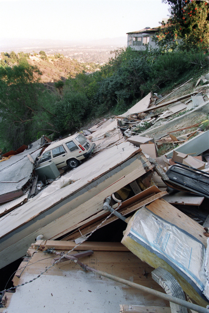 A car rests in the midst of a collapsed house in the hills north of Los Angeles, January 18, 1994, one day after Northridge earthquake.