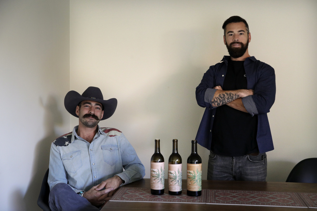 In this Friday, Dec. 22, 2017, photo, Alex Howe, right, and Chip Forsythe, co-founders of Rebel Coast, pause for photos with their cannabis-infused wine in Los Angeles. As the world's largest legal recreational marijuana market takes off in California, the trendsetting state is set to ignite the cannabis-culinary scene.