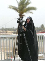 An Iraqi female journalist waits for the arrival of Iraqi Prime Minister Nuri al-Maliki during the inauguration of a newly built Tweirij Bridge across the Euphrates River in the city of Karbala, 110 kms from Baghdad on May 15, 2009. Maliki said that serious action will be taken against any corruption found within the Iraqi government. As the city of Karbala is considered a holy Shiite Muslim city, home to the Shrine of Imam Hussein, women cover up to show their respect.