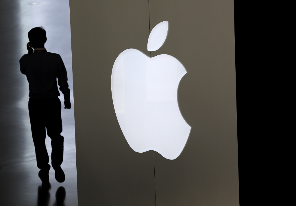File: A Chinese man talking on his smartphone walks into an Apple store in Beijing on Friday, Sept. 5, 2014.