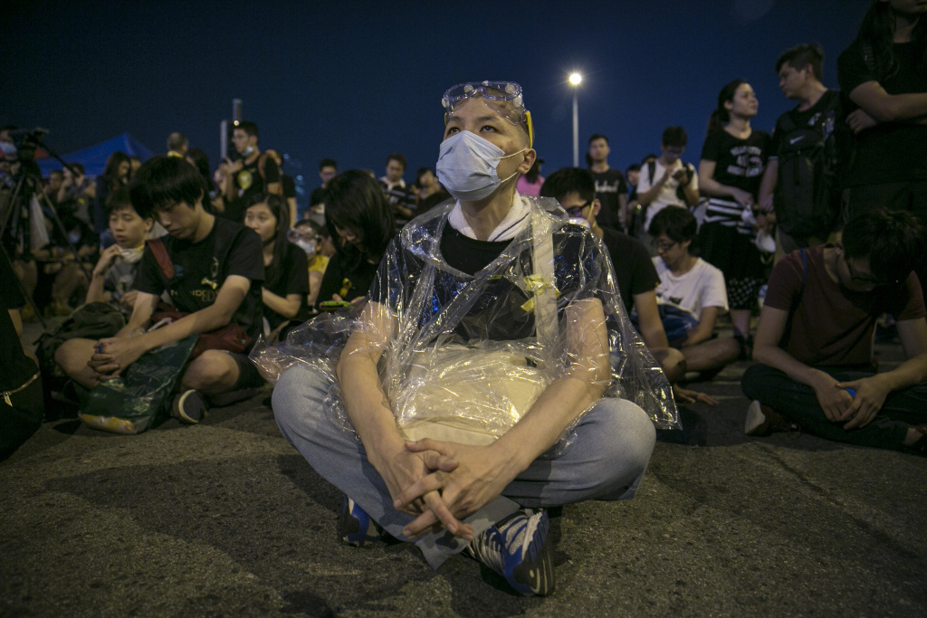 Protesters sit behind a government building as the standoff continues October 5, 2014 in Hong Kong, Hong Kong. Pro democracy supporters continue to occupy the streets surrounding Hong Kong's Financial district. Protesters have threatened to widen their campaign as they continue to call for open elections and the resignation of Hong Kong's Chief Executive Leung Chun-ying.