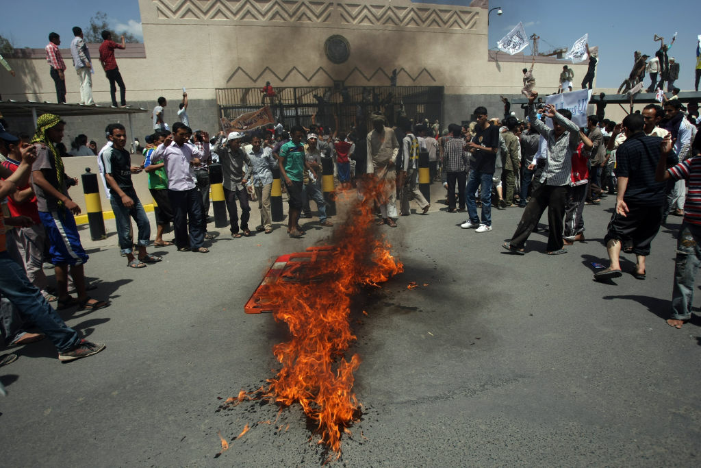 Yemeni protesters gather around fire during a demonstration outside the US embassy in Sanaa over a film mocking Islam on September 13, 2012. Yemeni forces managed to drive out angry protesters who stormed the embassy in the Yemeni capital with police firing warning shots to disperse thousands of people as they approached the main gate of the mission.