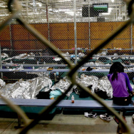 Two young girls watch a World Cup soccer match on a television from their holding area where hundreds of mostly Central American immigrant children are being processed and held at the U.S Customs and Border Protection Nogales Placement Center in Nogales, Ariz. on June 18.