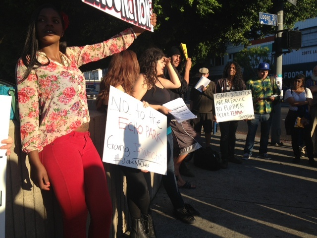 Activists with the Youth Justice Coalition rally against the proposed gang injunction on a street corner in Echo Park on National Night Out Day.