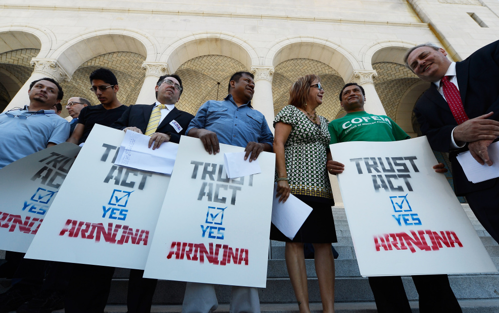 LOS ANGELES, CA - JUNE 26:  Activists, community leaders and speakers attend a rally and a news conference by the Coalition for Humane Immigrant Rights of Los Angeles regarding the U.S. Supreme Court's decision on the Arizona immigration law at Los Angeles City Hall on June 26, 2012 in Los Angeles, California. The U.S. Supreme Court struck down key parts of an Arizona law, but let stand a provision allowing police to check a person's immigration status while enforcing other laws. AB 1081 (the TRUST Act), would give local governments the right to opt-out of the controversial Secure Communities program. (Photo by Kevork Djansezian/Getty Images)