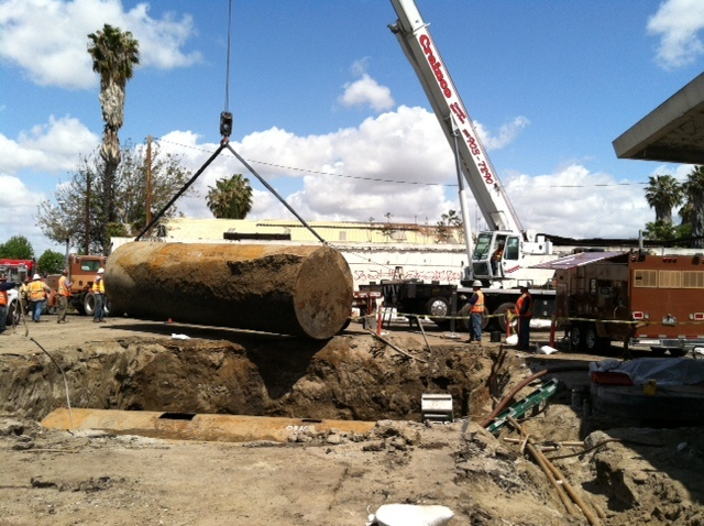 A crane lifts out a 10,000 gallon underground storage tank at a abandoned gas station in Compton. US EPA will remove tanks from 29 sites near the the 710 Freeway.