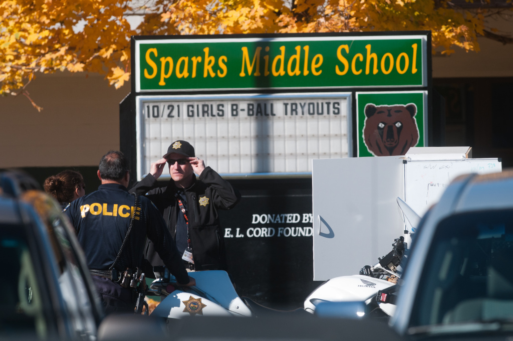 Law enforcement gather in the parking lot after a shooting at Sparks Middle School October 21, 2013 in Sparks, Nevada. A staff member was killed and two students were injured after a student opened fire at the Nevada middle school. The suspected shooter was also killed.
