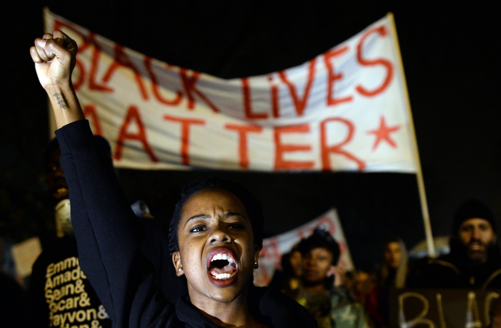 Demonstrators shout slogans during a march in St. Louis, Missouri, on November 23, 2014 to protest the death of 18-year-old Michael Brown. More than 100 protesters marched peacefully through St Louis on November 23, stepping up pressure on a grand jury to indict a white police officer for shooting dead an unarmed black teenager. Police stepped up security and erected barricades bracing for the worst with a grand jury to decide whether to indict the police officer. Brown was shot at least six times by police officer Darren Wilson in the St. Louis suburb of Ferguson on August 9, inflaming racial tensions and sparking weeks of protests, some violent.