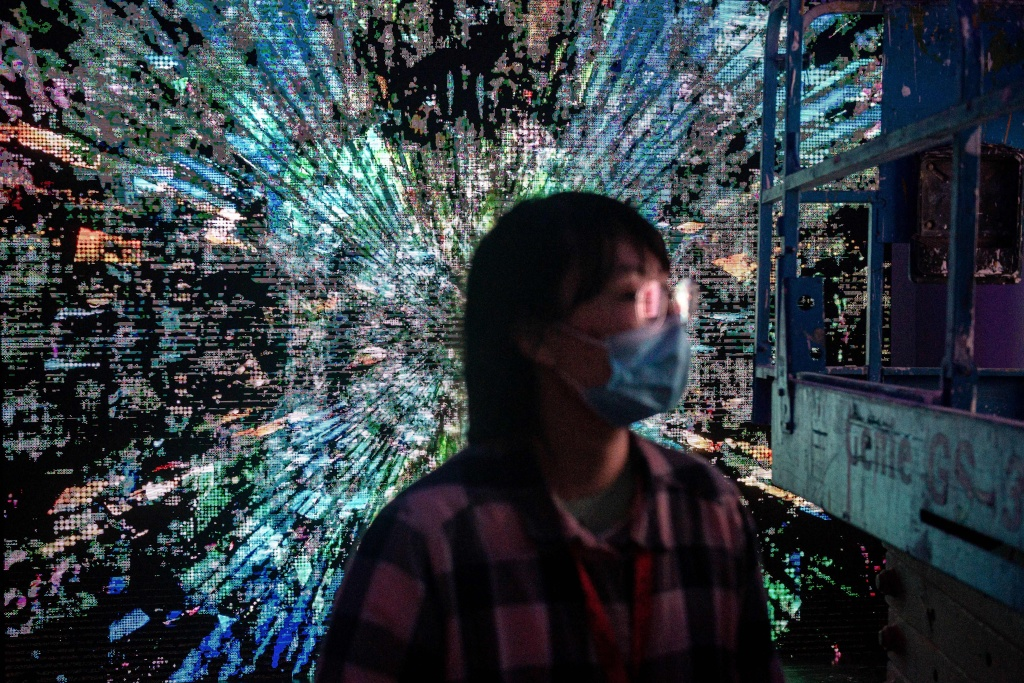 A woman walks in front of a digital painting by Chinese artist Liu Gang (back) at a crypto art exhibition in Beijing on March 26, 2021.