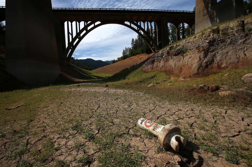 A buoy sits on dry cracked earth on a dry inlet of Shasta Lake on August 30, 2014 in Lakehead, California.