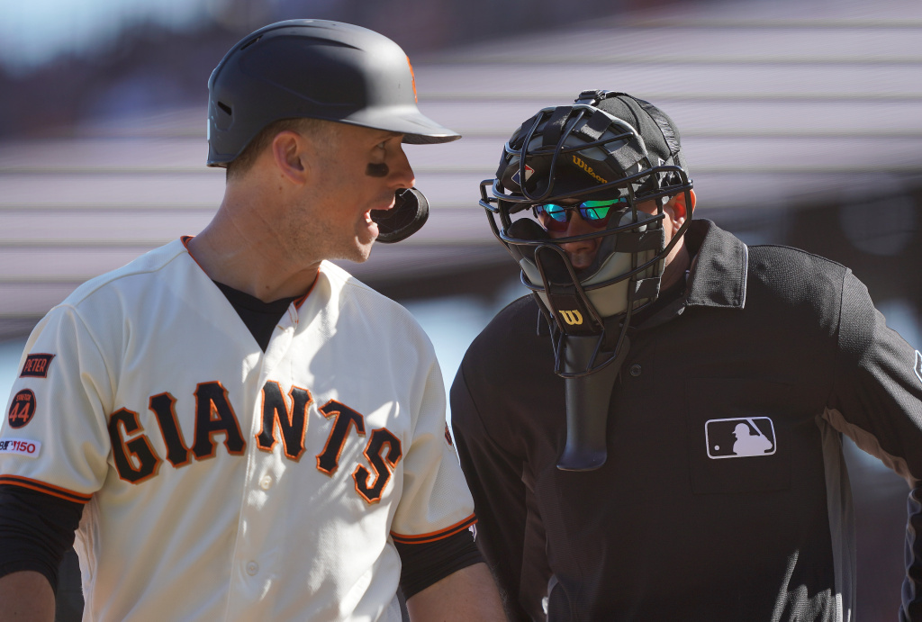 Buster Posey of the San Francisco Giants argues with home plate umpire Roberto Ortiz after Ortiz called Posey out on strikes against the Los Angeles Dodgers in the bottom of the eighth inning at Oracle Park on September 28, 2019 in San Francisco, California.