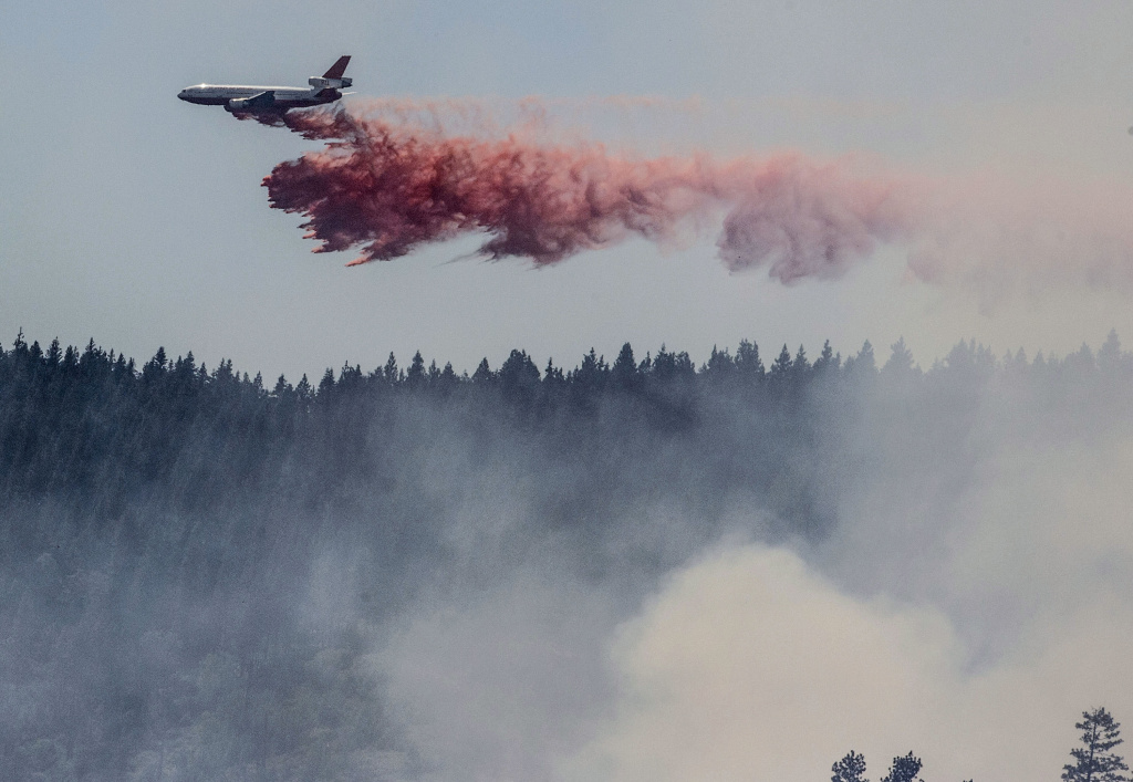 A plane drops fire retardant as firefighters battle a blaze in El Portal, Calif., near Yosemite National Park on Tuesday, July 29, 2014.