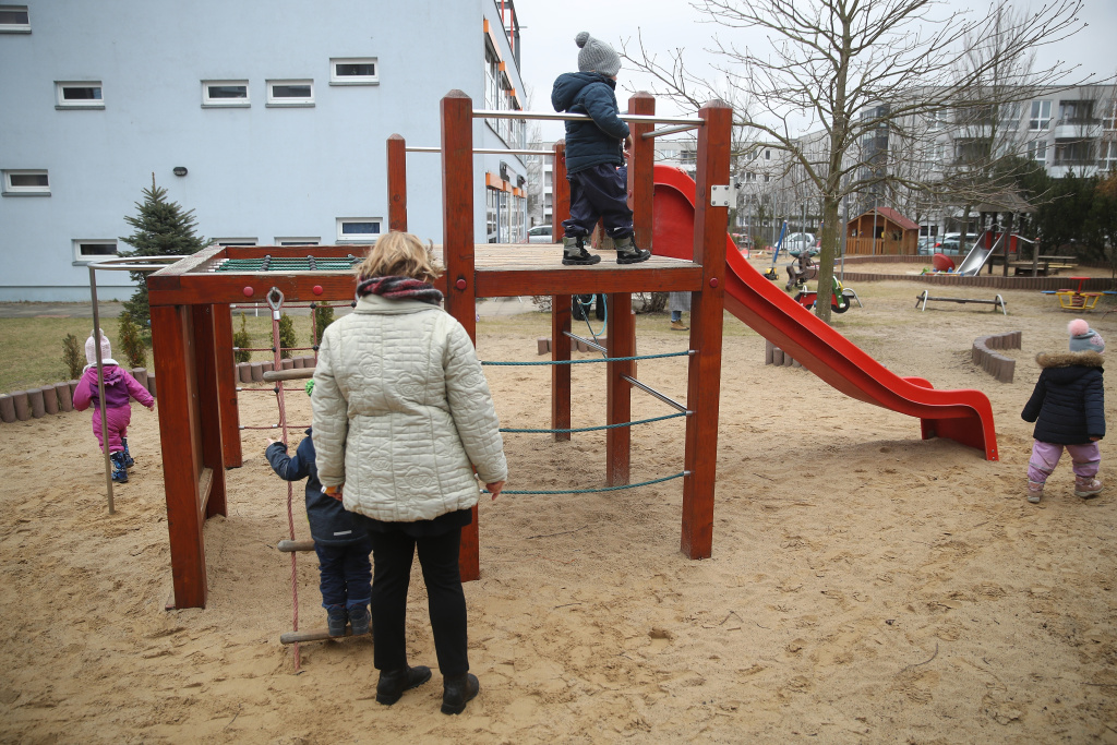 A nursery school teacher oversees children playing on a playground at the