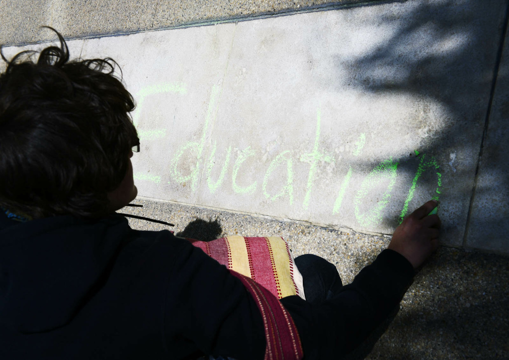 In this 2014 file photo, a student writes in chalk near the front entrance to the CSU Chancellor's office in Long Beach.