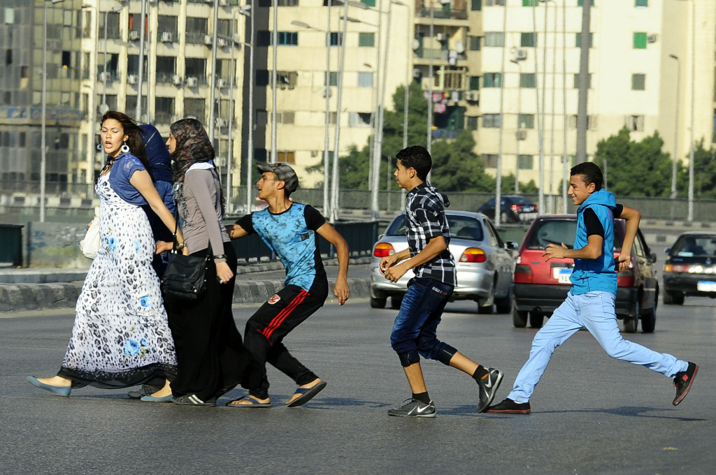 A youth, trailed by his friends, gropes a woman as she crosses a street in Cairo, Egypt.