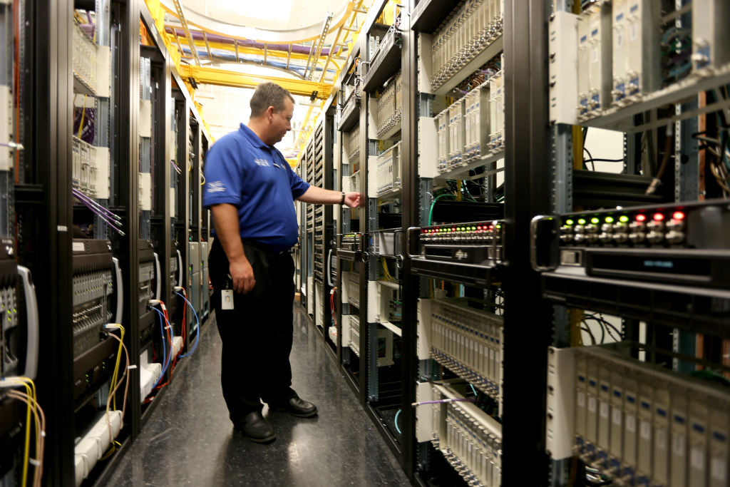 Brian Hunt, Director Engineering, South Florida, stands among the cables and routers at a Comcast distribution center where the Comcast regional video, high speed data and voice are piped out to customers on February 13, 2014 in Miramar, Florida. Comcast, which is seeking approval of a $45 billion purchase of Time Warner Cable, said it will extend beyond June its offer of low-cost broadband Internet for low-income families.