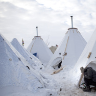 "Jacob Brooks makes adjustments to one of the camp's many ""tarpees,"" a winterized teepee made of tarp with a built-in chimney, designed by Paul Cheokoten Wagner. There are roughly 60 tarpees around various camps now, and Wagner has fundraised enough for another 20 more."