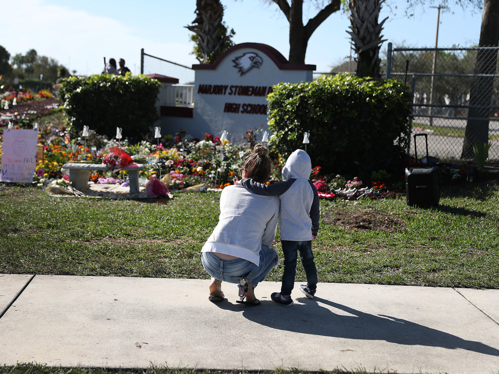 Jaxon Creed puts an arm around Destiny Calero, a 2013 graduate of Marjory Stoneman Douglas High School, at a memorial honoring those killed during a mass shooting there in February 2018. Florida's legislature has passed a bill allowing teachers to be armed.