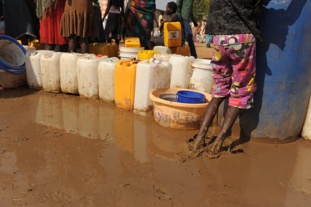 File: A young South Sudanese girl plays in the mud where women have queued up their jerrycans for water being distributed from a UN resevoir at the United Nations Mission in South Sudan (UNMISS) compound in Juba on December 21, 2013 where tension remains high fueling an exodus of both local and foreign residents from the south Sudanese capital. Brutal fighting in South Sudan has reopened deep-rooted ethnic divisions, forcing tens of thousands of terrified residents to seek shelter at UN bases or flee in fear of attacks. United Nations peacekeepers are currently sheltering over 35,000 civilians in various bases across the country, many belonging to the minority ethnic group in their respective areas.
